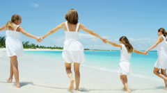 Happy Caucasian mother and daughters walking on a tropical beach - stock footage