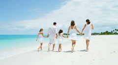 Young Caucasian parents and their female children enjoying a beach vacation - stock footage