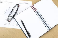 Workplace with pen, notebook, glasses and financial report Stock Photos
