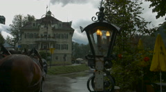 View of Schlosshotel Lisl, horses and a street light, Neuschwanstein Castle Stock Footage