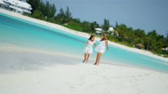 Barefoot young Caucasian girls walking together by a tropical ocean - stock footage