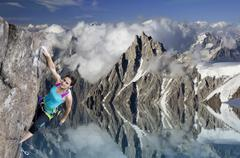 Female extreme climber hanging on cliff over the lake Stock Photos