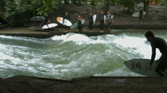 Man surfing on Eisbach in Munich Stock Footage