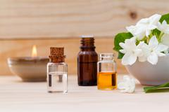 Aroma oil bottles arranged with jasmine flowers on wooden background . - stock photo