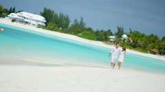 Caucasian couple walking together on a tropical vacation beach - stock footage