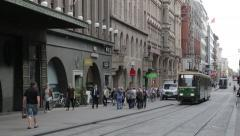 Trolley tram car going by with pedestrians on city street Stock Footage