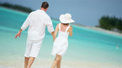 Happy young Caucasian couple in white clothing together on an island vacation - stock footage