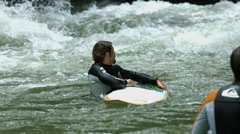 Man swimming on a surfboard and coming out of water, Munich Stock Footage