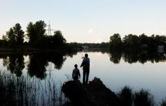 Father and son fishing with spinning rod on the lake Stock Photos
