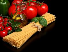 Long group of raw pasta tied with string isolated on black board with basil,t - stock photo