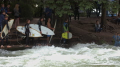 Girl surfing on Eisbach and five others surfers waiting their turn,  Munich Stock Footage