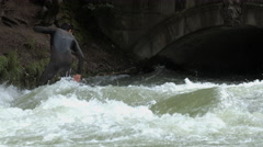 Man surfing on Eisbach near a bridge and coming out of water, Munich Stock Footage