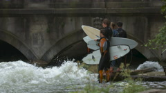 Four surfers waiting on the riverside and watching a surfer on Eisbach, Munich Stock Footage