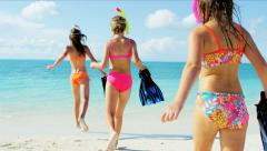 Happy young Caucasian sisters going snorkeling from a tropical beach - stock footage