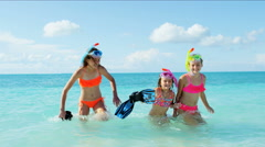 Young Caucasian girls in colorful swimwear snorkeling from a Caribbean beach - stock footage