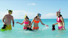 Happy Caucasian parents and young daughters snorkeling from a tropical beach Arkistovideo