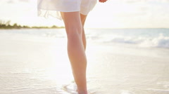 Legs of a Caucasian female walking barefoot on a beach - stock footage