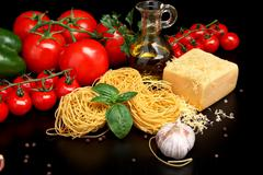 Round balls of pasta with tomatoes,basil,olive oil on black background - stock photo