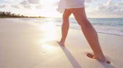 Legs of a Caucasian female walking barefoot on the beach - stock footage