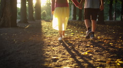Boy and Girl are Holding Hands Together and Walking at Park Stock Footage