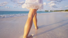 Female Caucasian barefoot on the beach at sunset - stock footage