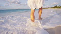 Legs of a barefoot Caucasian female enjoying island sunset Stock Footage