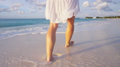 Caucasian female walking barefoot on the beach - stock footage