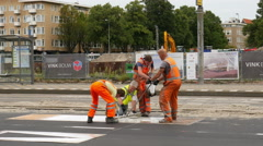 Workers apply paint for road sign Stock Footage