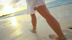 Female Caucasian legs barefoot on a beach at sunset - stock footage