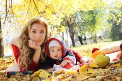 Mother and baby girl playing in autumn park - stock photo