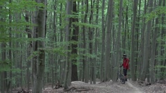 Downhill mountain biker resting at the start of a trail in a green forest. Stock Footage