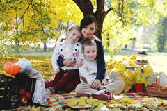 Mother with son and daughter under autumn trees - stock photo