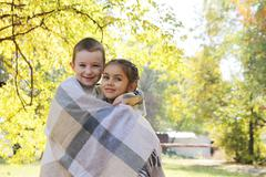 Sister and brother hugging in plaid under autumn trees - stock photo