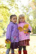 Stock Photo of Little girls in waterproof coats and boots in autumn park