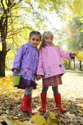 Little girls in waterproof coats and boots in autumn park - stock photo