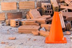 construction cone in construction site with bricks - stock photo
