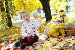 Girl showing hand-made pumpkin under autumn trees Stock Photos
