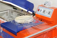 Packing industry equipment with pizza dough - stock photo