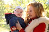 Stock Photo of Mother and baby girl laughing in autumn park