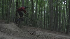 Downhill mountain bike ride in the dawn. The rider is taking a big jump. Stock Footage