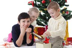 Mother and two children openning presents - stock photo