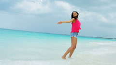 African American girl walking barefoot on ocean sand beach - stock footage