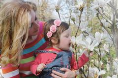 Stock Photo of Baby girl smelling magnolia blossom in spring