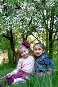 Girls sitting under spring tree - stock photo