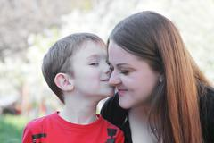Little brothet kissing sister on cheek Stock Photos