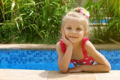 Stock Photo of Girl in the pool with one hand near cheek