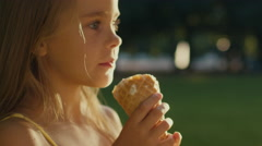 Stock Video Footage of Girl is Eating Ice Cream Outdoors
