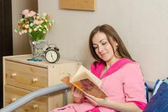 girl reading a book at bedtime - stock photo