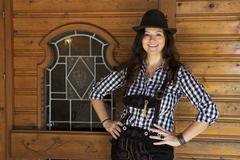 woman in lederhosen and bavarian hat - stock photo