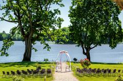 Lakeside wedding ceremony. Wedding chairs and wedding arch on a lawn - stock photo